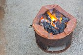 foto of brazier  - Charcoal brazier with cooking fire on cement ground - JPG