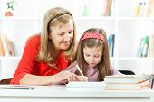 stock photo of grandmother  - Grandmother helping little girl to learn to write - JPG