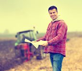 picture of tractor  - Happy young farmer with forms for bank loan standing on field tractor in background - JPG