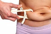 stock photo of fat woman  - Woman measuring fat belly - JPG