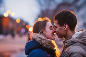 foto of rainy day  - Portrait of young beautiful couple kissing in an autumn rainy day - JPG