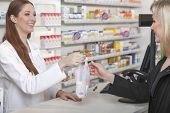 stock photo of sachets  - Friendly female pharmacist hands over a plastic sachet with medicine - JPG