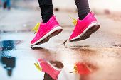image of rainy weather  - Unrecognizable young woman running in rainy weather - JPG