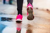 picture of rainy weather  - Unrecognizable young woman running in rainy weather - JPG