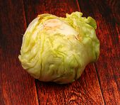 picture of iceberg lettuce  - isolated lettuce head on a wood table top - JPG