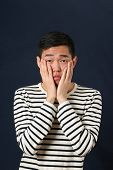 pic of disappointed  - Disappointed young Asian man covering his face by palms and looking at camera - JPG