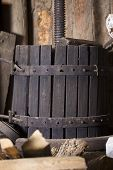 picture of wine-press  - Old manual grape pressing on wooden background - JPG