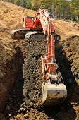stock photo of track-hoe  - Large track hoe excavator digging out old rock and soil during preperation at a new commercial development road construction project - JPG