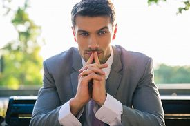 picture of sitting a bench  - Portrait of a businessman sitting on the bench outdoors and thinking - JPG