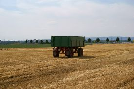 picture of tractor-trailer  - A tractor trailer stands on a mowed cornfield - JPG