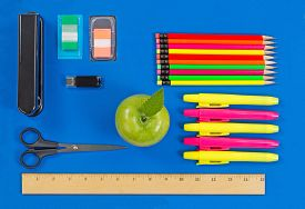 image of driving school  - Office or back to school supplies consisting of a green apple highlight markers stapler thumb drive ruler scissors tab markers and colorful pencils on blue background - JPG