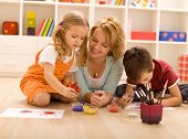 foto of family fun  - Woman having fun with kids laying on the floor painting hands - JPG