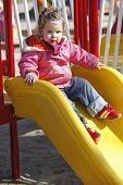 foto of chute  - young girl on chute on outdoor playground - JPG