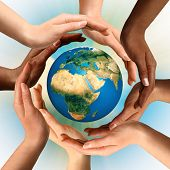 stock photo of world-globe  - Conceptual symbol of multiracial human hands surrounding the Earth globe - JPG