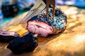 Cutting Delicious Roast Beef Pork Meat From Slow Cooking Smoker. poster