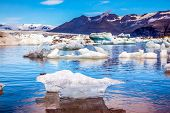Icebergs and ice floes are reflected in the smooth water. Drift ice Ice Lagoon - Jokulsarlon. Mornin poster