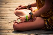 woman in a meditative yoga position sit on wooden pontoon on the lake wearing lot of bracelets and r poster