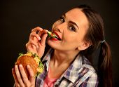Woman eating hamburger. Girl with flirty gaze wants to eat burger. Student consume fast food. Person poster