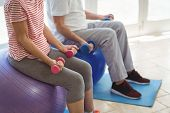 Senior couple exercising with dumbbells on exercise ball at home poster