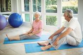 Happy senior couple interacting while performing exercise on exercise mat at home poster