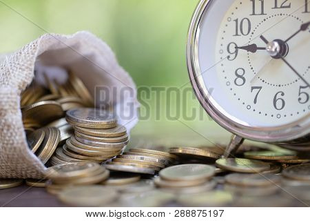 poster of Money Bags And Alarm Clock On Wooden Table With Nature Background,  Money Savings, Investment, Growi