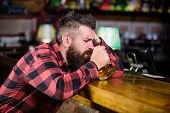 Man With Beard Spend Leisure In Dark Bar. Brutal Hipster Bearded Man Sit At Bar Counter Drink Beer.  poster
