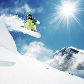 picture of jumping  - Snowboarder at jump inhigh mountains at sunny day - JPG