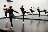 Female Students At Performing Arts School Rehearsing Ballet In Dance Studio Reflected In Mirror poster