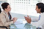 stock photo of negotiating  - Young business people negotiating in a meeting room - JPG