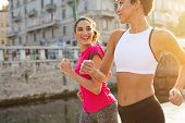 Two sporty women jogging in city. Multiethnic girls running on street at sunset. Two friendly fitnes poster