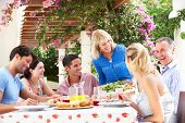 stock photo of grown up  - Group Of Young And Senior Couples Enjoying Family Meal - JPG