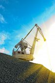 crane at heap of gravel on blue sky background