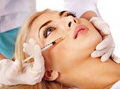stock photo of collagen  - Doctor woman giving botox injections - JPG