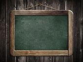 Aged green blackboard hanging on wooden wall as a background for your message