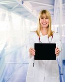 Happy Doctor Showing Digital Tablet in a passageway, indoor