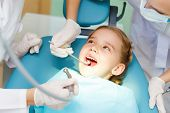 stock photo of cavities  - Little girl sitting in the dentists office - JPG