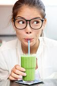 Green vegetable smoothie juice - woman hipster drinking smoothie as part of healthy eating lifestyle