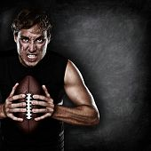 stock photo of stare  - Football player portrait holding american football staring aggressive looking at camera on black chalkboard background with copy space for text or design - JPG