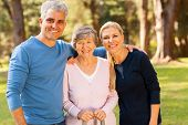 stock photo of mother law  - loving mid age couple and senior mother outdoors in forest - JPG