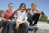 Portrait of happy teenage boys with skateboard sitting together in skate park