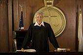 stock photo of proceed  - Portrait of confident senior female judge standing in court room - JPG