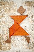stock photo of parallelogram  - abstract figure of a female dancer built from seven tangram wooden pieces - JPG