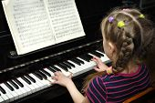 pic of musical instruments  - child plays on piano lesson of the music - JPG