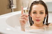 stock photo of soapy  - A young beautiful  woman is enjoying a bath with a glasses of champagne - JPG