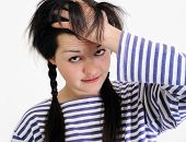 stock photo of dandruff  - worried young woman touching her hair looking at camera - JPG