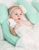 stock photo of tickling  - Portrait of very sweet and beautiful little baby child sitting in studio on the soft bed like a bride or princess in funny white and creamy costume with bare feet - JPG