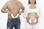 picture of nude couple  - Young couple holding socks front of belly - JPG
