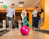 stock photo of bowler  - Group of four young smiling people playing bowling - JPG