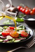 pouring olive oil on salad with tomato and cucumber