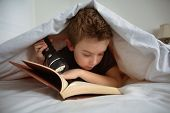 foto of laying-in-bed  - Boy reading under the covers - JPG